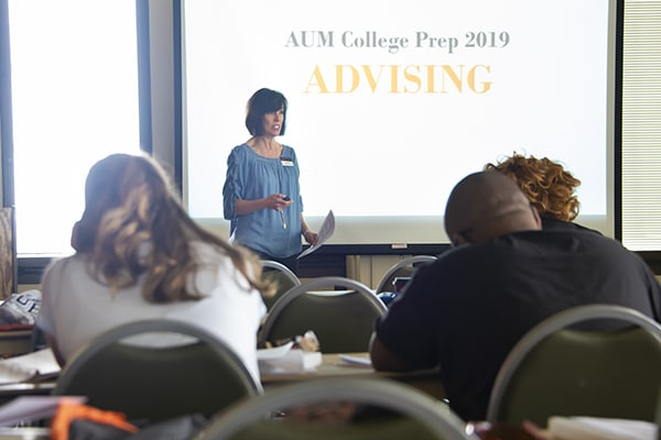 An advisor speaking to a large group of students