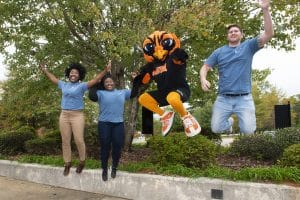 Jumping AUM students with warhawk mascot
